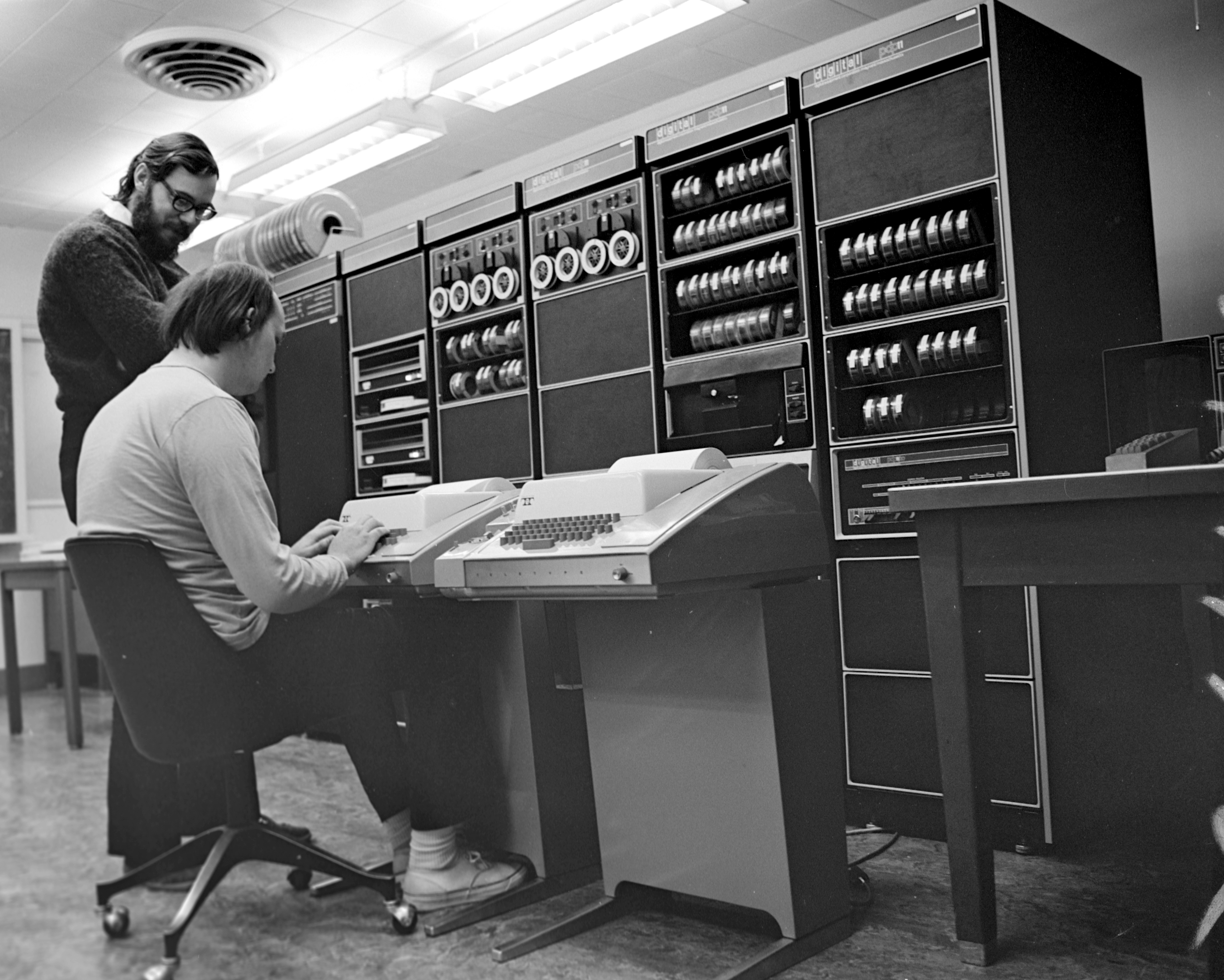 Image of Ken Thompson and Dennis Ritchie at work in 1972. Before them, a DEC PDP-11, with a Teletype Model 33 attached